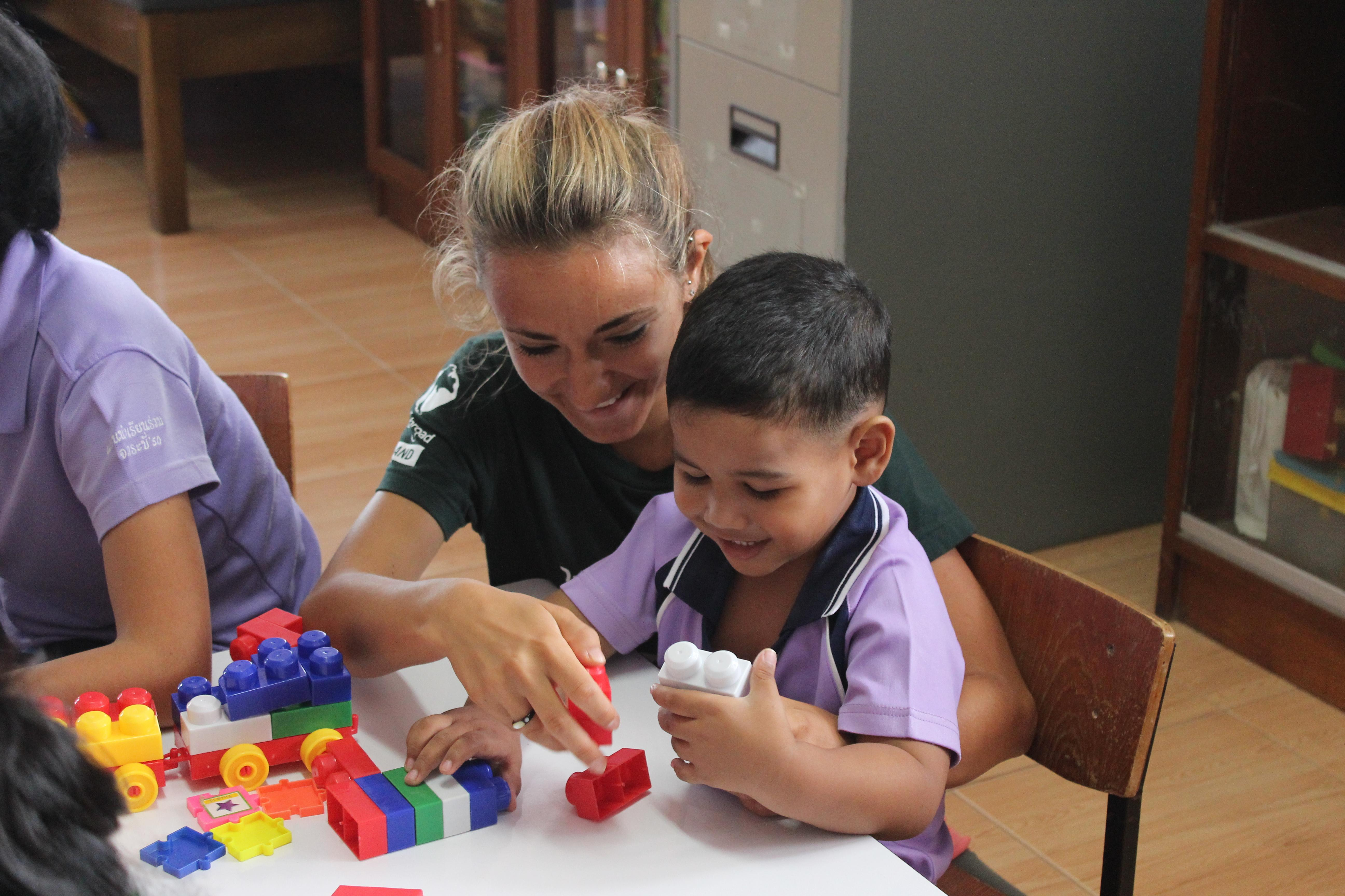 Female Childcare volunteer helps young boy build lego blocks in a day care centre during Care placement in Thailand.